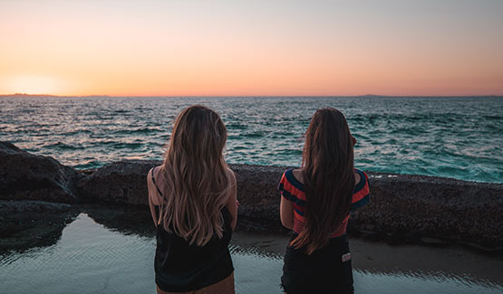 Two girls stand in front of the ocean